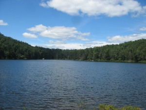 Blues skies above forested shores of Peaked Mountain Pond