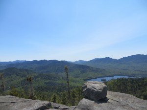 Large boulder atop mountain with high peaks wilderness area in the background