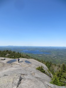Hiker atop Ampersand Mountain with Northern Adirondacks in the background